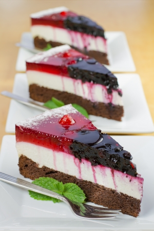 Delicious portions of forest fruit cake on plates photo
