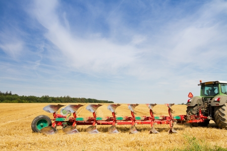 Agriculture tractor ready to plough stubble field under blue sky