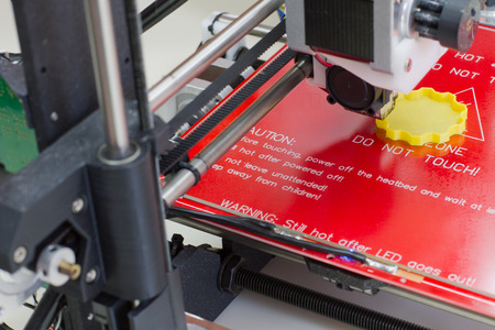 Detail of a 3D printer printing with a yellow ABS filament Banque d'images