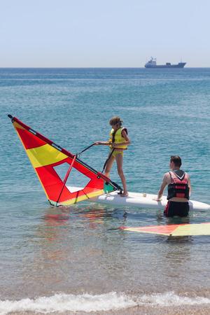 windsurf: Niña que toma la lección de windsurf y vela tirando del agua