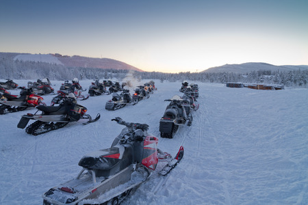 snowmobile: Group of snowmobiles ready for a ride in Lapland countryside Stock Photo