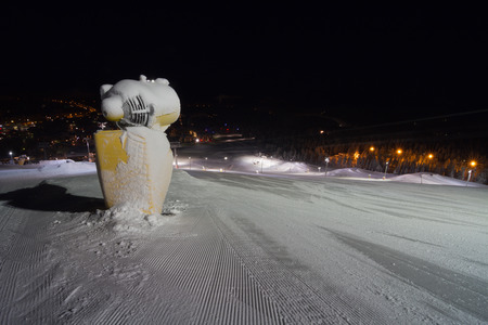 snow grooming machine: Snow machine gun at ski slope at ski resort Levi, Finland. Lights over ski slope and snow park in darkness