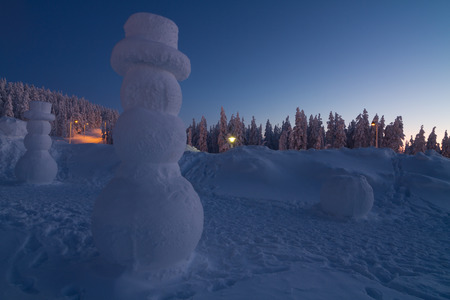 overlooking: Giant snowman overlooking winter landscape after sunset Stock Photo