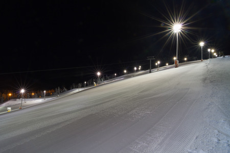 snow grooming machine: Ski slope ready for night skiing in Levi, Finland Stock Photo
