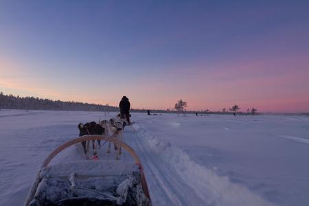 lapland: Husky sledge ride at sunset in winter wonderland (Lapland) Stock Photo