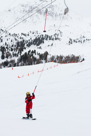 Little girl snowboarder rises up the mountain on ski tow in French Alps La Plagne