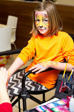 face paint: Pretty girl getting her hands and face painted as a tiger