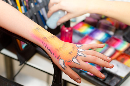 body painting: Detail of a girls hand getting painted as a tiger paw
