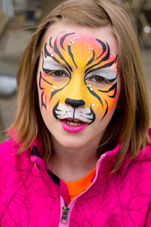 smile face: Pretty girl with her face painted as a tiger
