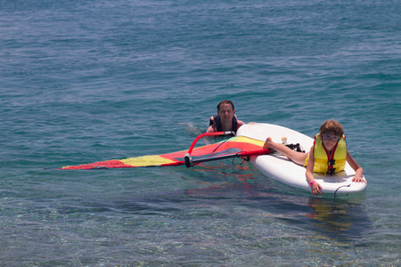9 10 years: Having fun at sea and beginner windsurfer girl on a surf