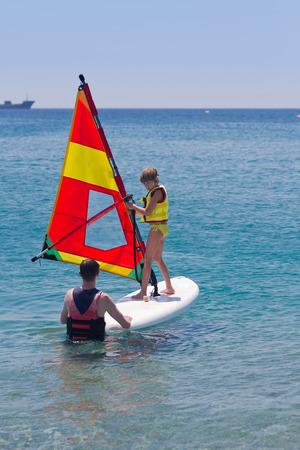 Kleines Mädchen, das Windsurfen Lektion über ein ruhiges Meer und sonnigen Tag