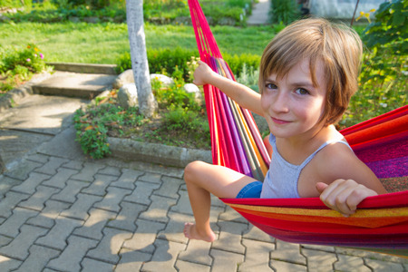 young girl barefoot: Lovely smiling girl relaxing in a hammock