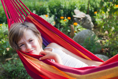9 10 years: Lovely smiling girl relaxing in a hammock in a garden