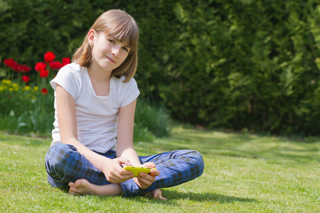 10 years old: Beautiful girl holding a smartphone in a garden on a sunny day Stock Photo