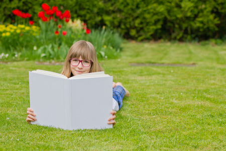 Beautiful girl reading a book wearing glasses and relaxing in a garden