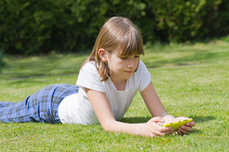 Beautiful girl holding a smartphone in a garden on a sunny day Banque d'images