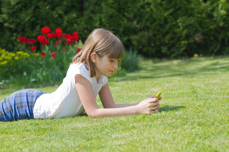 Beautiful girl holding a smartphone in a garden on a sunny day Stock Photo