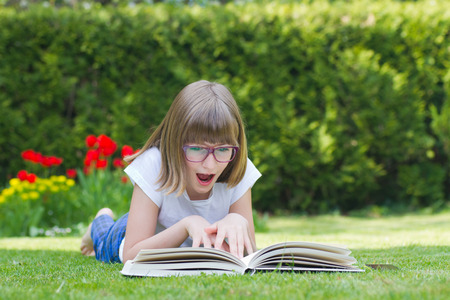 10 years old: Beautiful girl astonished by reading a book in a garden
