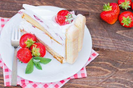 Delicious strawberry cake Charlotte on a wooden background