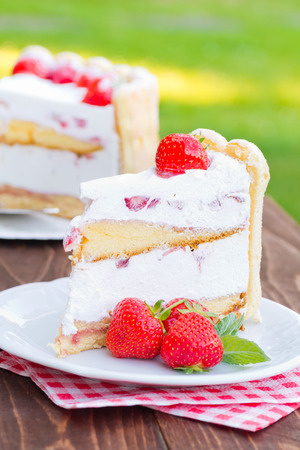 Delicious strawberry cream cake Charlotte on a wooden background
