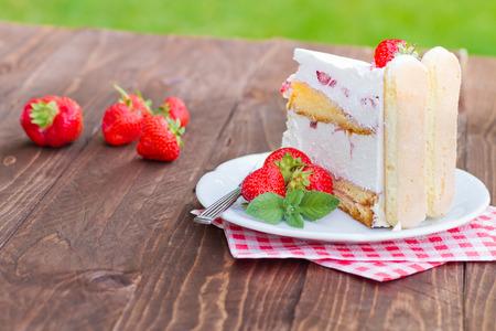 porcion de torta: Delicioso pastel de fresas Charlotte en un fondo de madera