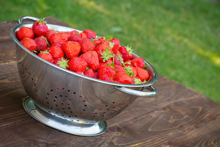 Freshly picked strawberries in a colander on a wooden table Stock Photo