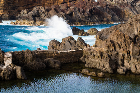 Volcanic lava cliffs separating an ocean from calm natural swimming lagoon in Porto Moniz, Madeira, Portugal