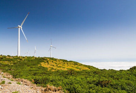 Spectacular view in Paul da Serra highlands in Madeira island, Portugal. Low vegetation, wind turbines and clouds below in a valley. Stock Photo