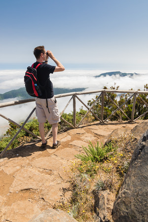 uplands: A man standing on a viewpoint above clouds, looking into binoculars and admiring a spectacular view in Paul da Serra plateau in Madeira island, Portugal, on a beautiful sunny day. Stock Photo