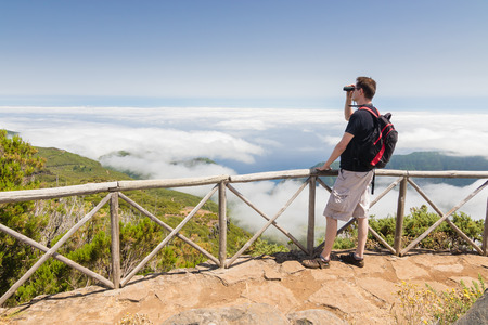 A man standing on a viewpoint above clouds, looking into binoculars and admiring a spectacular view in Paul da Serra plateau in Madeira island, Portugal, on a beautiful sunny day. Stock Photo