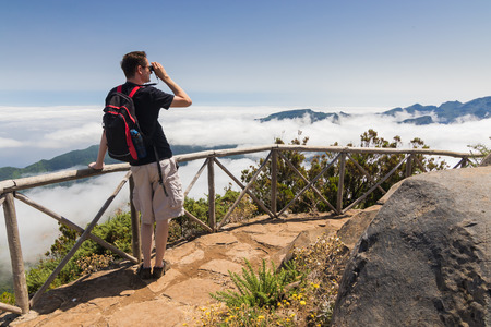 uplands: A man standing on a viewpoint above clouds, looking into binoculars and admiring a spectacular view from Paul da Serra plateau towards Pico Ruivo. Beautiful sunny day in Madeira island, Portugal