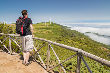 uplands: A man standing on a viewpoint above clouds and admiring a spectacular view of Paul da Serra plateau with wind turbines in Madeira island, Portugal, on a beautiful sunny day.