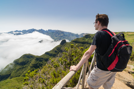 spectacular: A man standing on a viewpoint above clouds and admiring a spectacular view from Paul da Serra plateau over Pico Ruivo mountain, in Madeira island, Portugal, on a beautiful sunny day.