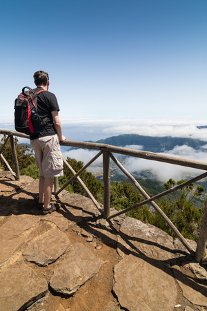 uplands: A man standing on a viewpoint above clouds and admiring a spectacular view from Paul da Serra plateau towards Sao Vicente valley. Beautiful sunny day in Madeira island, Portugal.