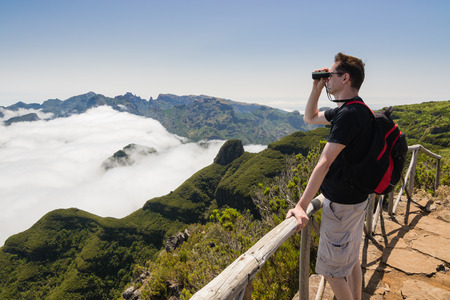 uplands: A man standing on a viewpoint above clouds, looking into binoculars and admiring a spectacular view from Paul da Serra plateau over Pico Ruivo mountain, in Madeira island, Portugal, on a beautiful sunny day.