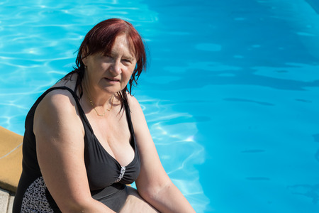 senior woman: Portrait of a senior active woman smiling and sitting at the border of an outdoor swimming pool