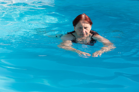 Active senior woman swimming and relaxing in a swimming pool on a sunny summer day