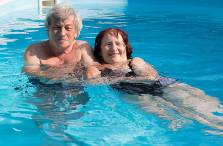 swimming: Smiling senior couple enjoying time together in a swimming pool on a sunny day