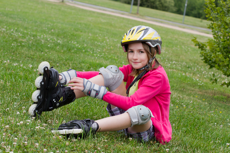 10 years girls: A girl putting on her roller skates in a park Stock Photo