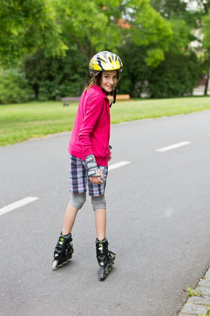 10 years girls: Smiling girl enjoying rolller skating in a park with a turned head backwards and looking into camera Stock Photo
