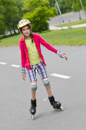 inline skater: Smiling girl enjoying rolller skating in a town park and looking into camera