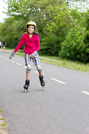 10 years girls: Smiling girl enjoying rolller skating in a park, wearing protective helmet and looking at camera