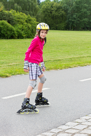 girl legs: Smiling girl enjoying rolller skating in a park and looking into camera Stock Photo