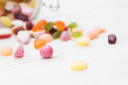 Open glass jar full of different colourful jelly candies on white wooden background