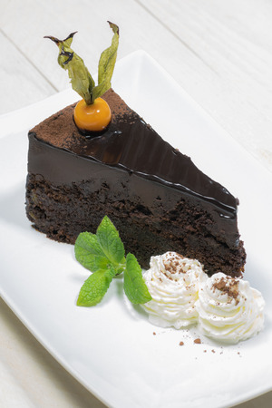 garnish: Portion of a sacher cake with physalis garnish and whipped cream Stock Photo