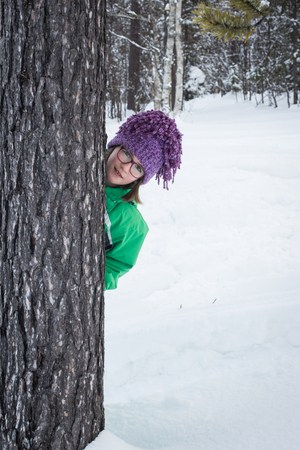 causasian: Cute littel girl wearing glasses and hiding in a snowy forest