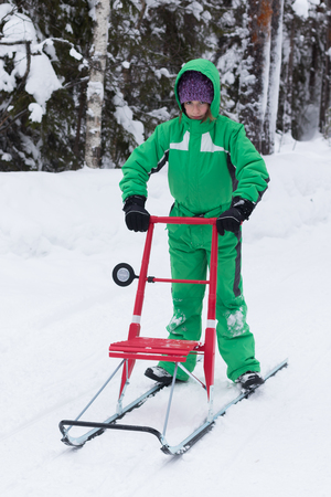 Little girl riding a kicksled - traditional Finnish means of transport in snowy winter