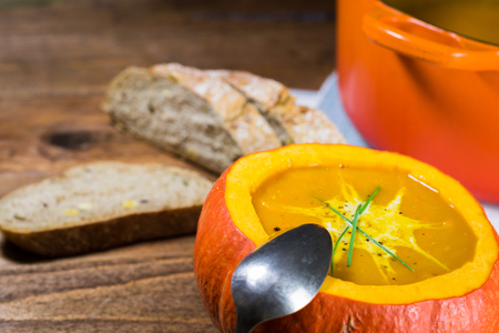 Fresh creamy pumpkin soup served in a pumpkin and garnished with parsley Stock Photo
