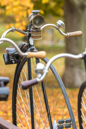 velocipede: A penny-farthing bicycle with an old headlamp in a park with fallen autumn leaves Stock Photo