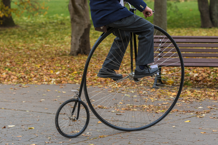 wheeler: An unidentified men riding a penny-farthing bicycle in a park with fallen autumn leaves Stock Photo